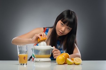 Half-length portrait of pretty young dark-haired Asian woman sitting at the table squeezing juice from oranges and lemons using juicer very diligently  Isolated on black background photo