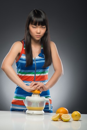 Half-length portrait of young tired dark-haired Asian woman standing at the table squeezing juice from oranges and lemons using juicer very diligently  Isolated on black background photo