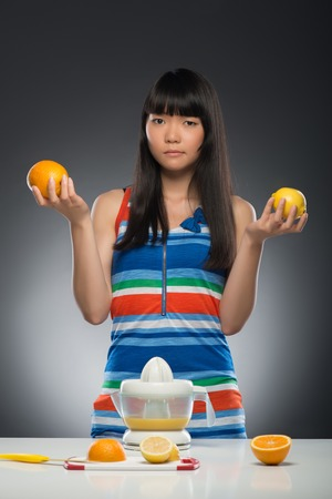 Half-length portrait of young smiling dark-haired Asian woman standing at the table with juicer on it holding orange in one hand and lemon in another decided what kind of juice she wants  Isolated on black background photo