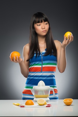 Half-length portrait of young smiling dark-haired Asian woman standing at the table with juicer on it holding orange in one hand and lemon in another decided what kind of juice she wants  Isolated on black background