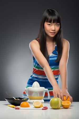 Half-length portrait of pretty young dark-haired Asian woman standing at the table with juicer and fruits on it choosing orange  Isolated on black background photo