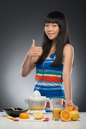 Half-length portrait of pretty young smiling dark-haired Asian woman standing at the table with juicer and fruits on it showing us that she likes juice very much  Isolated on black background photo