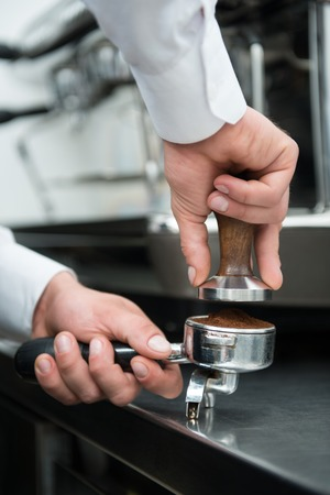 Selected focus on the hands of professional barista pressing coffee using the pounder with wooden handle  Coffee machine on background