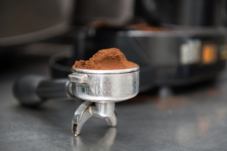Selected focus on the ground coffee in special form of coffee machine photo