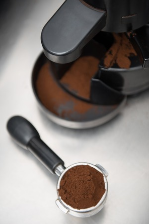 coffeemaker: Ground coffee in the holder of coffee machine lying near the coffeemaker  Top view