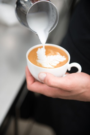 Selected focus on the hands of professional barista holding a cup of coffee and making the pattern with the help of milk on it photo