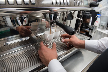 Hands of professional barista standing near the big metal coffee machine and looking how coffee pouring into the white cups