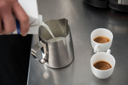 Two cups of americano standing on the bar counter near the metal jar for milk photo