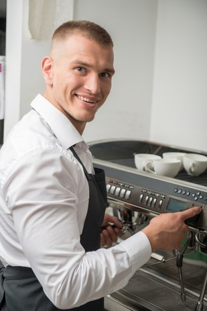 Half-length portrait of handsome young smiling barista making coffee for us using coffee machine photo