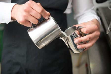 Professional barista wearing white shirt and black apron pouring milk from big metal jar to the small one photo