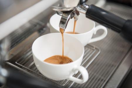 tazas de cafe: Dos tazas blancas de pie en la rejilla de la m�quina de caf� y el caf� que vierte en ellos Foto de archivo