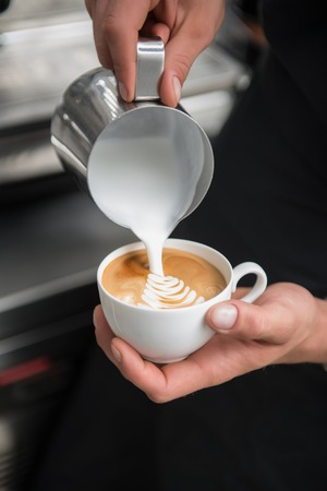 Selected focus on the professional barista pouring milk into the cup of coffee making a pattern