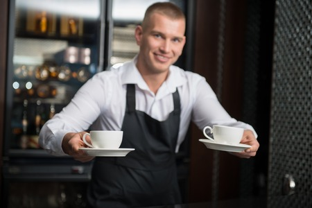suggested: Selective focus on two white cups in the hands of handsome young smiling barista wearing white shirt and black apron suggested us to taste his coffee on background