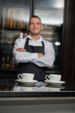 Selective focus on two white cups of coffee standing on the bar counter  Young smiling barista with crossed arms on background