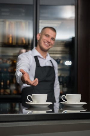 suggested: Selective focus on two white cups on the bar counter  Handsome young smiling barista wearing white shirt and black apron suggested us to taste his coffee on background