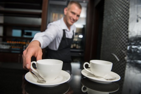 Selective focus on two white cups of coffee on the bar counter  Handsome young smiling barista wearing white shirt and black apron touching one of them on background photo