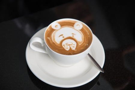 Cup of aromatic tasty cappuccino with the pattern of teddy bear