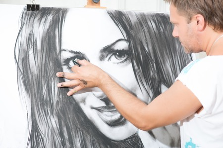 brash: Handsome fair-haired painter drawing his wonderful picture with the charcoal Stock Photo