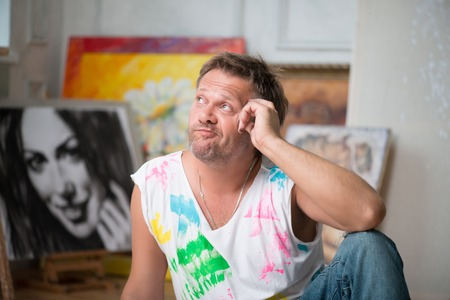 brash: Selected focus on fair-haired painter wearing painted white shirt and blue torn jeans sitting on the floor in his workshop thinking about her life  His pictures on background