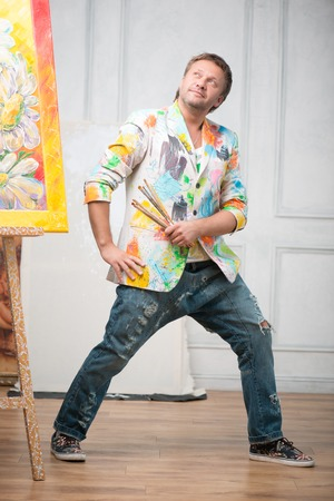 brash: Full-length portrait of happy fair-haired painter wearing painted white colorful jacket and blue torn jeans standing near his picture with the brushes in his hands satisfied with his work Stock Photo