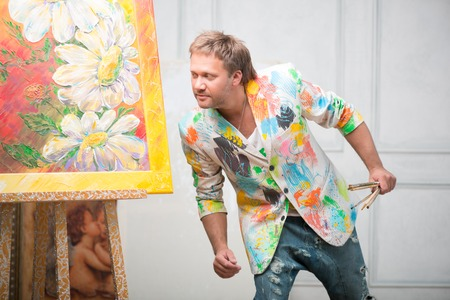 brash: Half-length portrait of fair-haired cool painter wearing white painted jacket and torn jeans holding brushes in his hand standing near his picture and looking at it very carefully Stock Photo