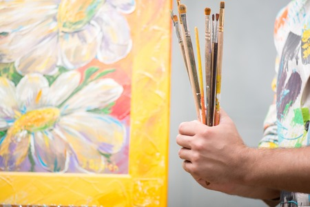 Painter wearing white painted jacket holding a pile of different brushes in his hand standing near his lovely picture  Stock Photo