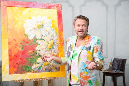 Half-length portrait of fair-haired happy painter wearing white painted jacket standing with brushes and showing us his great picture Stock Photo