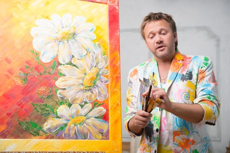 Half-length portrait of fair-haired concerned painter wearing white painted jacket standing near his picture with the brushes in his hands retelling us about hard work of painter Stock Photo