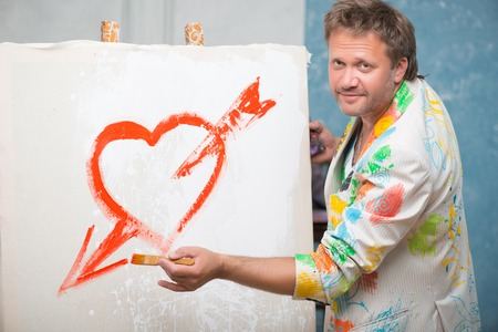 Half-length portrait of fair-haired painter wearing cool painted jacket standing aside picturing nice red heart with arrow on the white linen