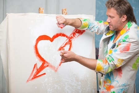 brash: Half-length portrait of fair-haired painter wearing cool painted jacket standing aside picturing nice red heart with arrow on the white linen