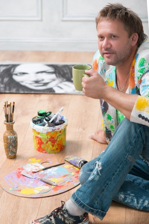 brash: Portrait of thoughtful fair-haired painter wearing cool painted jacket and torn jeans sitting on the floor in his studio near his famous picture having a rest with the cup of tea Stock Photo