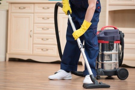 Selective focus on janitor wearing blue overalls vacuuming the floor in the office  Commode on background