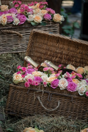 coronet: Selective focus on wonderful twisted basket of different kind of roses and three bottles of champagne in it