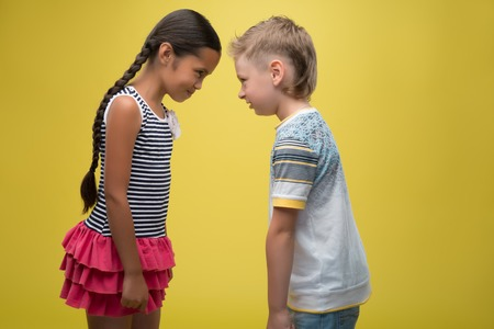 glowering: Half-length portrait of pretty dark-haired little girl wearing nice striped dress and little fair-haired boy standing aside glowering at each other. Isolated on yellow background  Stock Photo
