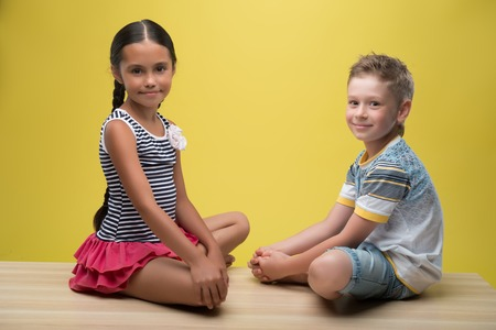 fair haired: Half-length portrait of pretty dark-haired little girl wearing nice striped dress sitting opposite little fair- haired smiling boy wearing T-shirt and blue baggies. Isolated on yellow background