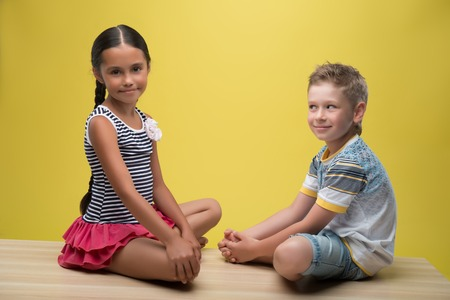 Half-length portrait of pretty dark-haired little girl wearing nice striped dress sitting opposite little fair- haired smiling boy wearing T-shirt and blue baggies. Isolated on yellow background  photo