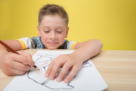blond haired: Little smiling fair-haired funny boy wearing nice colored T-shirt sitting at the table drawing a picture. Isolated on yellow background Stock Photo