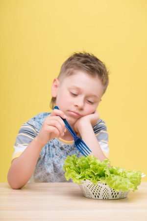 plateful: Half-length portrait of lovely little fair-haired thoughtful boy wearing T-shirt sitting at the table dawdling in the plateful of lettuce