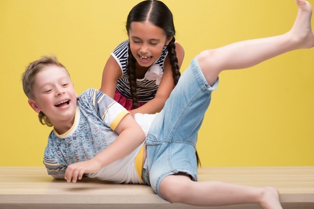 Half-length portrait of pretty dark-haired smiling little girl wearing nice striped dress tickling a cute fair-haired boy having a fun. Isolated on yellow background  photo