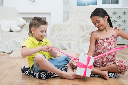 Portrait of two lovely smiling kids sitting on the floor in their house untying pink band of the present  Stock Photo