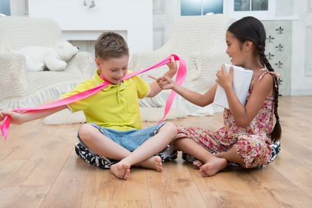Full-length portrait of fair-haired smiling boy wearing yellow T-shirt and blue baggies holding a long pink band from the present which is kept by nice dark-haired girl sitting on the floor  Stock Photo