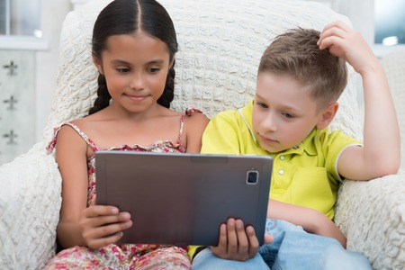 Portrait of two lovely kids sitting in the great cozy armchair looking on the tablet thinking about something  photo