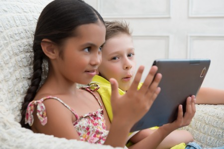 Portrait of two lovely kids sitting aside in the great cozy armchair looking at something on the tablet spend good time together photo