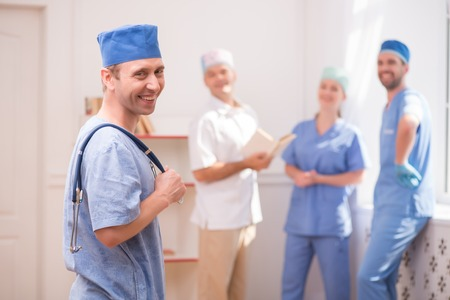 Selective focus on smiling doctor wearing blue medical dress standing aside keeping a stethoscope and looking at us. His smiling colleagues standing near the window on background Stock Photo