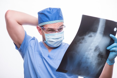 dudando: Retrato de medio cuerpo del doctor vestido azul vestido vacilante m�dico mirando la imagen de rayos X. Aislado en el fondo blanco Foto de archivo
