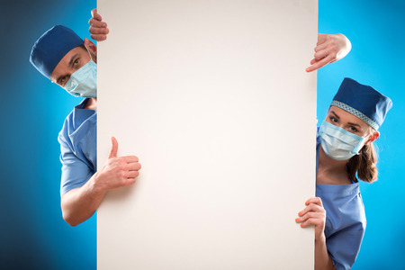 orderly: Portrait of two doctors wearing blue medical uniform and masks looking out of the huge poster for copy place. Isolated on blue