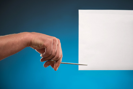 White sheet of paper for copy place is held by someone with the help of scissors. Isolated on blue  photo