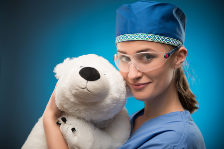 Half-length portrait of fair-haired lovely nurse wearing blue medical uniform and glasses showing us her wonderful white teddy bear. Isolated on blue background photo