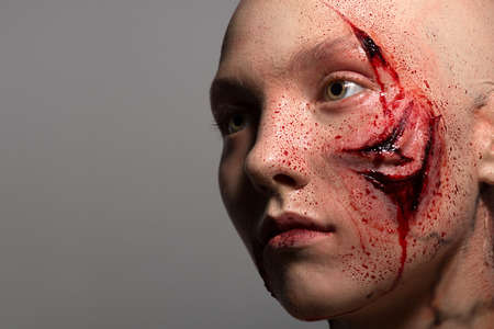 gash: Woman getting into the accident having a big terrible gash on her face isolated on grey background