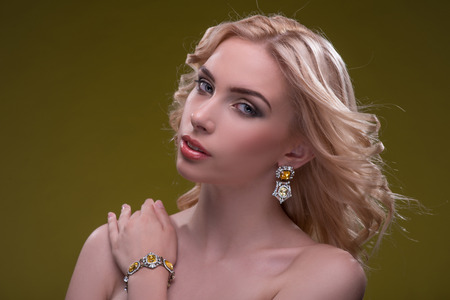 fingering: Half-length portrait of beautiful sexy blonde with evening make up wearing great diamond earrings fingering and bracelet putting her hand on her shoulder looking at us isolated on dark background
